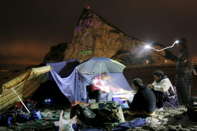 Spanish fishermen eat on a beach while an outline of the Queen Elizabeth II is seen projected on the Rock of the British Colony of Gibraltar to celebrate her 90th birthday, from La linea de la Concepcion, southern Spain April 21, 2016. (Photo by Jon Nazca/Reuters)