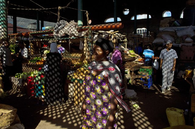 A woman walks through a spice market in Mombasa's old town  on April 4, 2014. The open sided market was established in 1914 and has changed little since its conception. (Photo by Carl de Souza/AFP Photo)