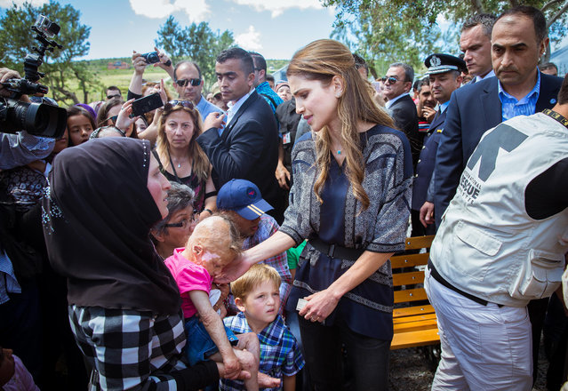 In this picture provided by the Office of Her Majesty's Press Department, Queen Rania of Jordan, center, touches an injured baby during her visit to Kara Tepe municipality camp in the Greek island of Lesbos, Monday, April 25, 2016. (Photo by Office of Her Majesty Press Department via AP Photo)