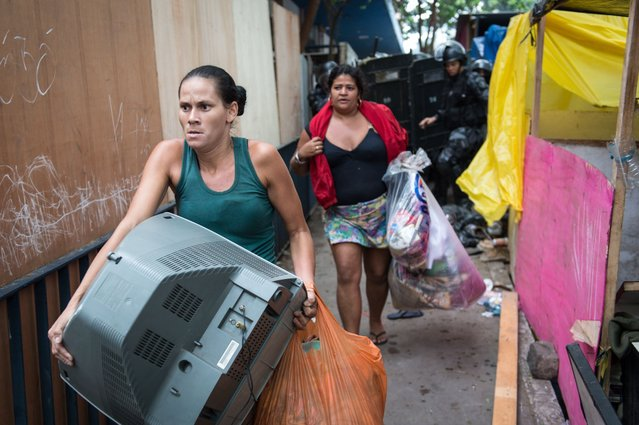 Squatters who were occupying an abandoned lot leave carrying their belongings after being evicted by police in Rio de Janeiro, Brazil, on April 11, 2014. (Photo by Yasuyoshi Chiba/AFP Photo)