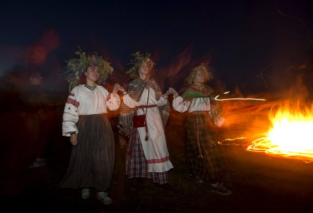 Belarusian women dance as they take part in the Ivan Kupala festival near the town of Rakov, west of Minsk June 27, 2015. (Photo by Vasily Fedosenko/Reuters)