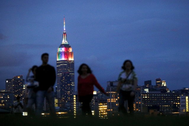 People walk in Hoboken's park as The Empire State Building is lit in rainbow colors during the celebration of the annual Gay Pride Parade in New York June 28, 2015. (Photo by Eduardo Munoz/Reuters)