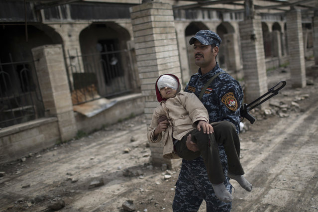 A Federal Police officer carries an injured boy through a destroyed train station during fighting between Iraqi security forces and Islamic State militants, on the western side of Mosul, Iraq, Sunday, March 19, 2017. The battle for western Mosul, including the narrow alleyways of the old city, looks to be the most devastating yet for Iraqi civilians trapped between advancing troops and increasingly desperate Islamic State militants. An estimated 750 civilians have been killed or wounded since the push to retake the western half of the city began in late January, and more than 100,000 have fled. (Photo by Felipe Dana/AP Photo)