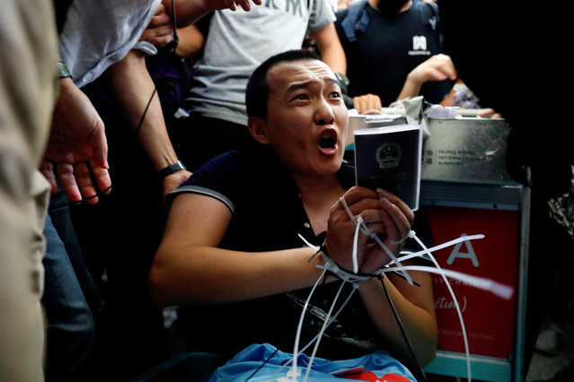 Fu Guohao, reporter of Chinese media Global Times website, is tied by protesters during a mass demonstration at the Hong Kong international airport, in Hong Kong, China, August 13, 2019. (Photo by Tyrone Siu/Reuters)