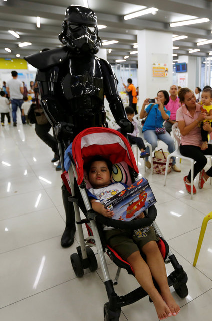 A child in a stroller reacts as it is pushed by a member of a Star Wars fan club in Thailand, dressed as a Shadow stormtrooper during Star Wars Day celebration at the Queen Sirikit National Institute of Child Health in Bangkok, Thailand, May 4, 2016. (Photo by Chaiwat Subprasom/Reuters)