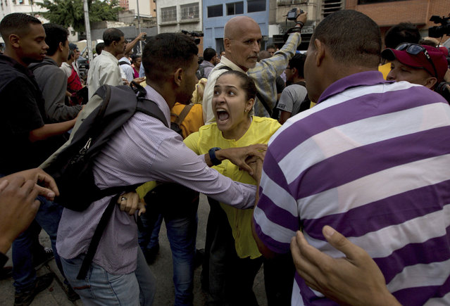 An opposition member, center, argues with a supporter of Venezuela's President Nicolas Maduro during a protest outside of Venezuela's General Prosecutor's office in Caracas, Venezuela, Friday, March 31, 2017. Venezuelans have been thrust into a new round of political turbulence after the government-stacked Supreme Court gutted congress of its last vestiges of power, drawing widespread condemnation from foreign governments and sparking protests in the capital. (Photo by Fernando Llano/AP Photo)