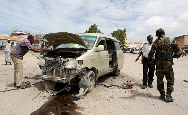 Somali soldiers and explosion experts assess the wreckage of a car, which belonged to an intelligence security officer, after it was destroyed in a blast in the Hamar Weyne district of Somalia's capital Mogadishu July 5, 2015. The officer and a policeman were injured in the explosion, according to a government official at the scene. (Photo by Feisal Omar/Reuters)