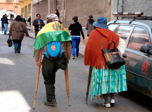 A couple with physical disabilities walk after a rally protest calling on the government to provide a monthly subsidy rather than an annual one, in La Paz, Bolivia, May 5, 2016. (Photo by David Mercado/Reuters)