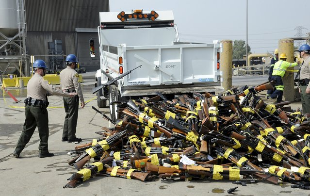 Los Angeles County Sheriff deputies assist with the destruction of approximately 3,400 weapons during the 22nd Annual Gun Melt in Rancho Cucamonga, California July 6, 2015. The confiscated weapons by Los Angeles County and ten participating law enforcement agencies will be melted down to convert the weapons into construction steel rebars for use in local highways and bridges. (Photo by Bob Riha, Jr./Reuters)