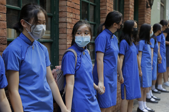 """Students wearing mask hold hands to surround St. Stephen's Girls' College in Hong Kong, Monday, September 9, 2019. Thousands of demonstrators in Hong Kong urged President Donald Trump to """"liberate"""" the semiautonomous Chinese territory during a peaceful march to the U.S. Consulate on Sunday, but violence broke out later in the business and retail district as police fired tear gas after protesters vandalized subway stations, set fires and blocked traffic. (Photo by Kin Cheung/AP Photo)"""