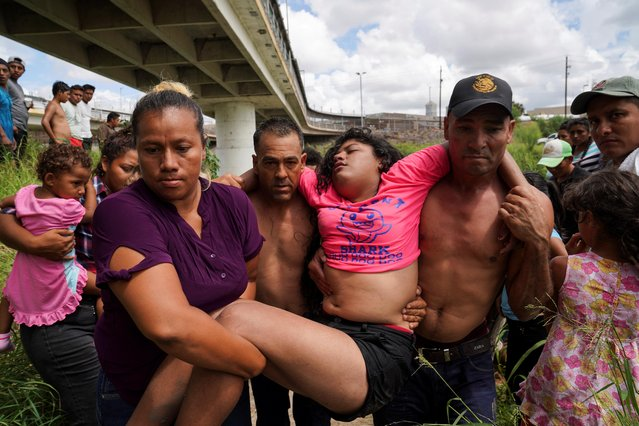"Brenda, a Honduran girl who is seeking asylum in the U.S., is carried from the Rio Grande in distress, where she had been bathing across the river from a Brownsville, Texas U.S. Customs and Border Protection tent facility as immigration hearings were being held by video teleconference, in Matamoros, Mexico September 12, 2019. Most of the people living in an encampment near the Gateway International Bridge have been sent back under the ""Remain in Mexico"" program, officially named Migrant Protection Protocols (MPP). (Photo by Veronica G. Cardenas/Reuters)"