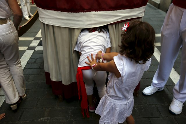 "A girl pushes another to get inside a giant during San Fermin festival's ""Comparsa de gigantes y cabezudos"" (Parade of the Giants and Big Heads) in Pamplona, northern Spain, July 10, 2015. (Photo by Susana Vera/Reuters)"