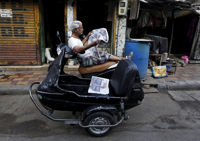 A man reads a newspaper as he sits on his scooter outside a shop in Ahmedabad April 8, 2015. (Photo by Amit Dave/Reuters)