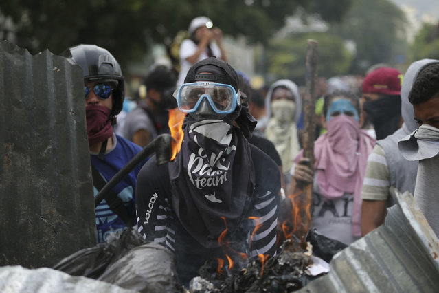 Anti-Government protesters stand at a barricade in Caracas, Venezuela, Wednesday, April 19, 2017. (Photo by Fernando Llano/AP Photo)