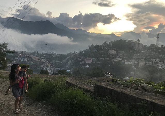 A Naga girl carries a child and walks up a slope during sunset in Kohima, capital of the northeastern Indian state of Nagaland, Thursday, September 19, 2019. Nagas are indigenous people living in several northeastern Indian states and across the border in Myanmar. (Photo by Yirmiyan Arthur/AP Photo)