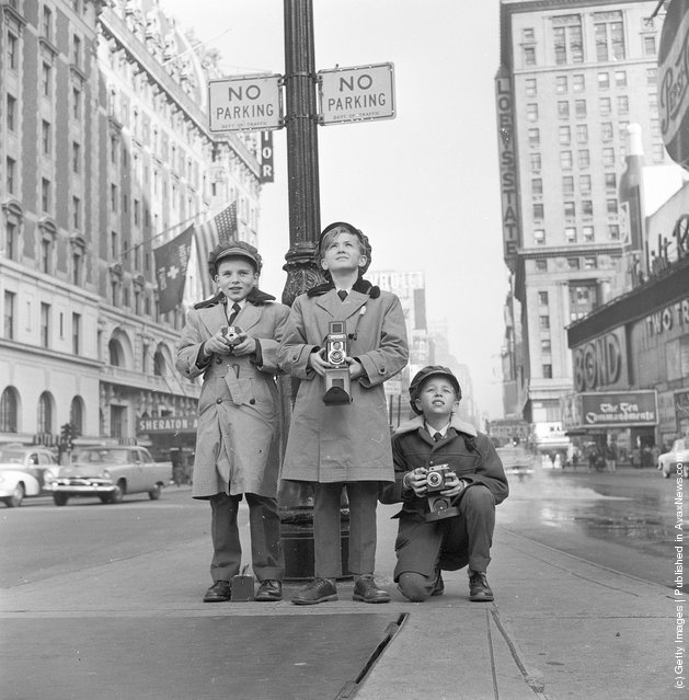 1956: Choristers from a Norwegian choir on a visit to New York take photographs in Times Square