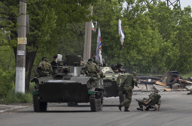 Pro-Russian armed men ride on top of an armoured personnel carrier near the town of Slaviansk, eastern Ukraine, May 5, 2014. Pro-Russian separatists ambushed Ukrainian forces on Monday, triggering heavy fighting on the outskirts of the rebel stronghold of Slaviansk, Interior Minister Arsen Avakov was quoted as saying. (Photo by Baz Ratner/Reuters)