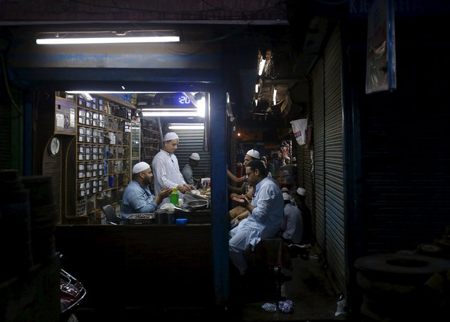 Muslims offer prayers before having their Iftar (breaking of fast) meal inside a shop during the holy month of Ramadan in the old quarters of Delhi, India, July 10, 2015. (Photo by Anindito Mukherjee/Reuters)