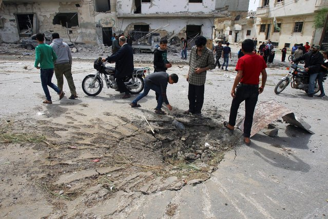 People inspect a site hit by an airstrike in the rebel-controlled city of Idlib, Syria May 13, 2016. (Photo by Ammar Abdullah/Reuters)