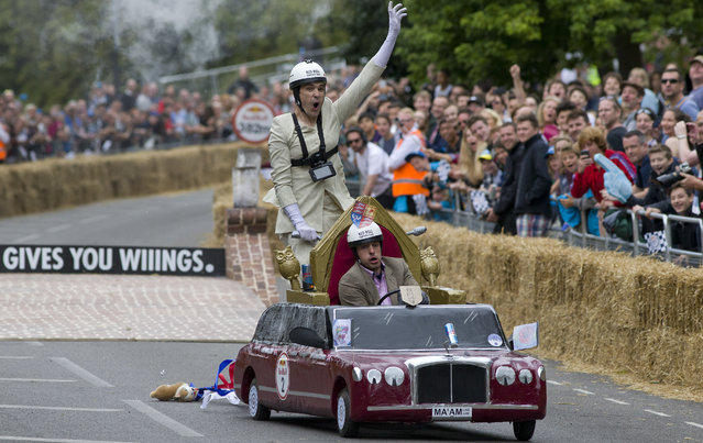 A team competes in the Red Bull Soapbox race in London on July 12, 2015. The Red Bull Soapbox race is an annual event where amateur drivers race with their homemade soapbox vehicles down a 420m hill through obstacles. (Photo by Justin Tallis/AFP Photo)