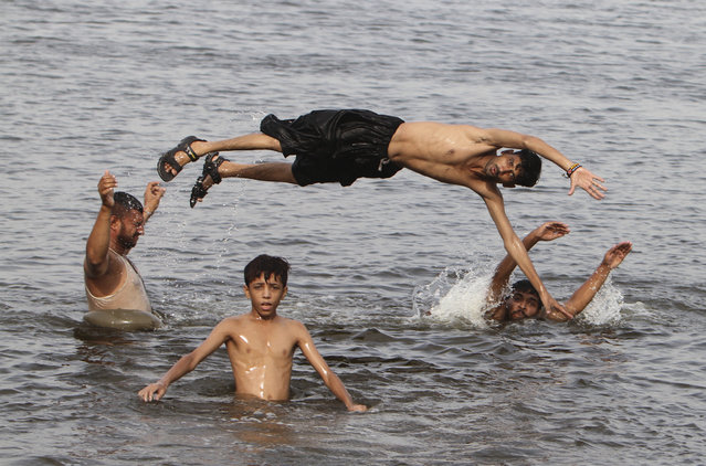 People cool themselves off in a water during a hot weather in Karachi, Pakistan, Wednesday, July 1, 2015. More than 1,200 people lost their lives due to a weeklong heat wave in the southern port city of Karachi, suffering from heatstroke and dehydration. (Photo by Fareed Khan/AP Photo)
