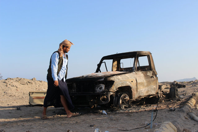 A man walks past a vehicle after an Apache helicopter from a Saudi-led military coalition fired a missile at it outside Aden International Airport, Yemen February 12, 2017. (Photo by Reuters/Stringer)