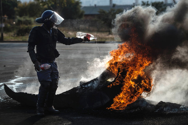 A South African policeman attempts to extinguish a fire after demonstrators burnt tyres to barricade a road, during violent protest demanding better housing on May 11, 2015 in Finetown, Ennerdale, South Africa. (Photo by Mujahid Safodien/AFP Photo)