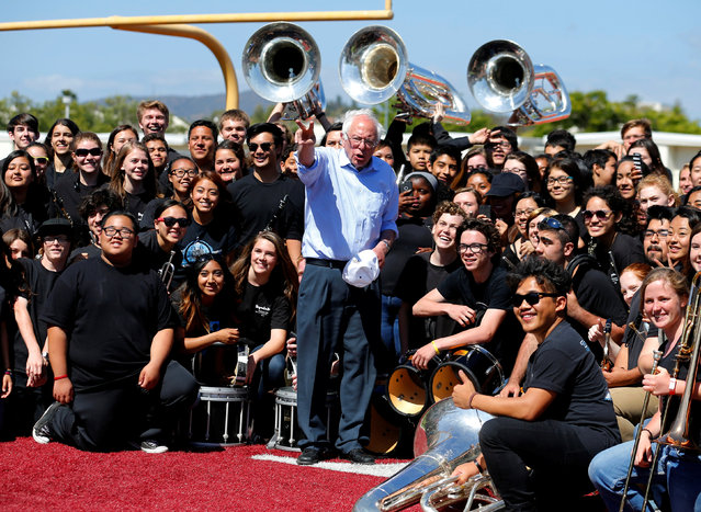U.S. Democratic presidential candidate Bernie Sanders organizes a picture with the Rancho Buena Vista High School marching band after they played at a rally for Sanders at their High School in Vista, California, United States May 22, 2016. (Photo by Mike Blake/Reuters)