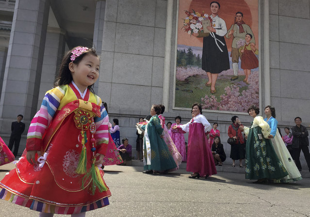 A young girl watches as North Korean men and women take part in a mass dance on Tuesday, April 25, 2017, in Pyongyang, North Korea. Pyongyang residents hold mass dances across the city to mark the 85th anniversary of the country's army. Despite deepening tensions on the Korean Peninsula, and reports of a major military drill on the country's east coast, the North's capital was quiet. (Photo by Eric Talmadge/AP Photo)