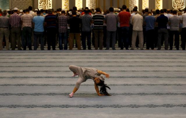 A girl plays as worshippers attend night prayers at Ahmet Hamdi Akseki Mosque in Ankara, Turkey July 14, 2015. (Photo by Umit Bektas/Reuters)