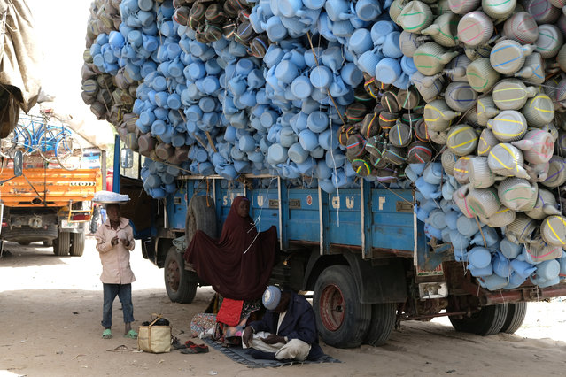 A family of refugees shelters under a truck carrying plastic lota, kettles used to perform Muslim ablutions in Muna Garage, Maiduguri, Nigeria February 16, 2017. (Photo by Paul Carsten/Reuters)