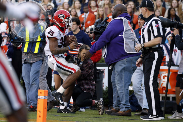 Georgia running back Brian Herrien (35) runs out of bounds and into a photographer during the first half of an NCAA college football game against Auburn, Saturday, November 16, 2019, in Auburn, Ala. (Photo by Butch Dill/AP Photo)