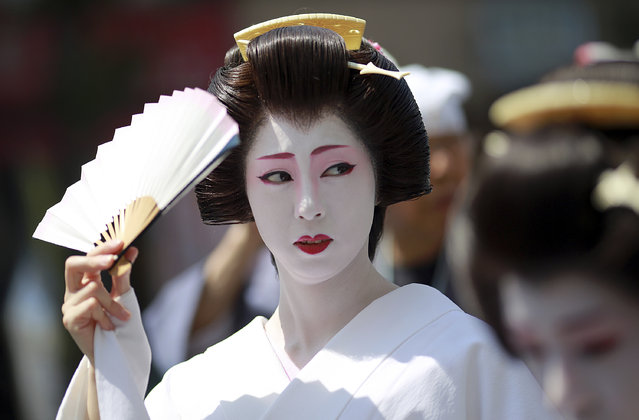 Geisha women parade down the street to Asakusa Shrine in the compound of Sensoji Temple Friday, May 19, 2017, in Tokyo prior to the annual Sanja Festival, one of the three major festivals in Tokyo. (Photo by Eugene Hoshiko/AP Photo)