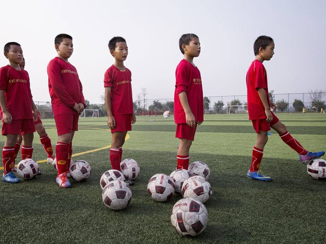Students wait to kick during training at the Evergrande International Football School near Qingyuan in Guangdong Province. (Photo by Kevin Frayer/Getty Images)