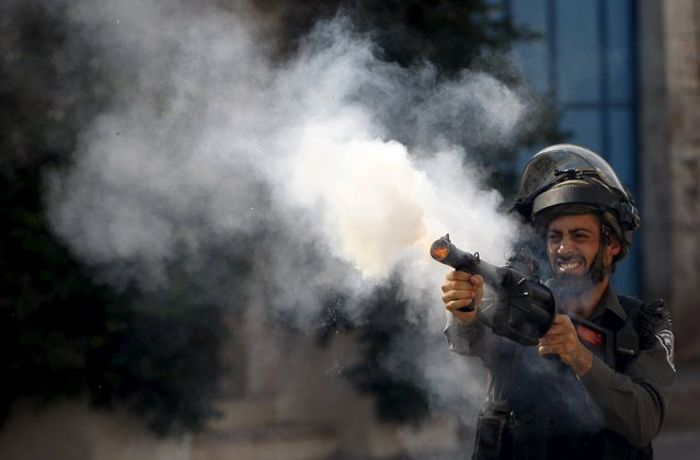 An Israeli border policeman fires tear gas canisters during clashes with Palestinian protesters in the West Bank city of Hebron July 31, 2015. (Photo by Mussa Qawasma/Reuters)