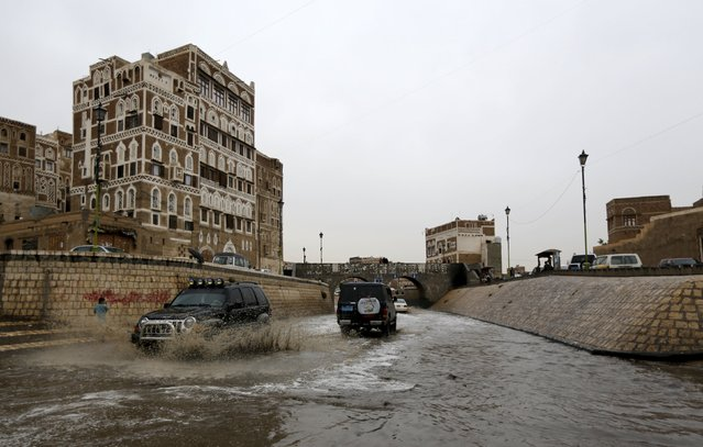 Cars drive in floodwaters during a rainy day in the old quarter of Yemen's capital Sanaa August 1, 2015. (Photo by Khaled Abdullah/Reuters)