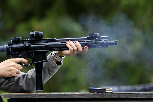 A woman shoots her rifle at a forest shooting range near the village of Visnova, Czech Republic, June 9, 2016. (Photo by David W. Cerny/Reuters)