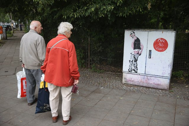 An elderly couple stop to look at street art at an intersection in Friedrichshain district on June 26, 2014 in Berlin, Germany. Berlin, with its long tradition of counter-culture, has become a mecca for street art of all dimensions and messages. (Photo by Sean Gallup/Getty Images)