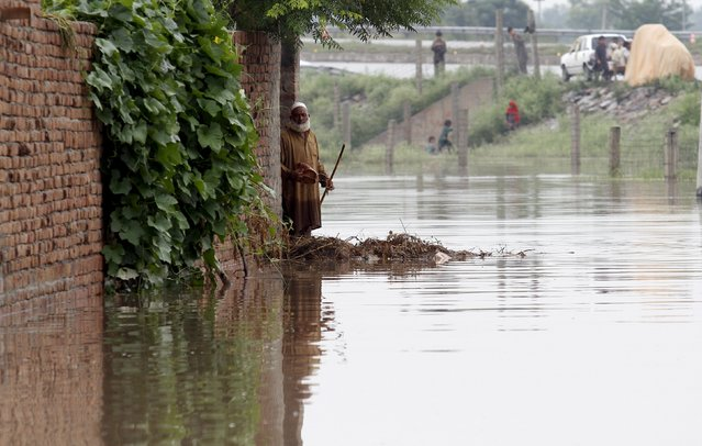 An elderly man waits for rescue crews for evacuation beside his home in Camp Koruna Akbar in the Pura area of Nowshera District, northwestern Pakistan, August 2, 2015.  Flash flooding caused by torrential monsoon rains affected hundreds of thousands of people, according to aid agencies, with further monsoon downpours expected in the coming days. (Photo by Fayaz Aziz/Reuters)