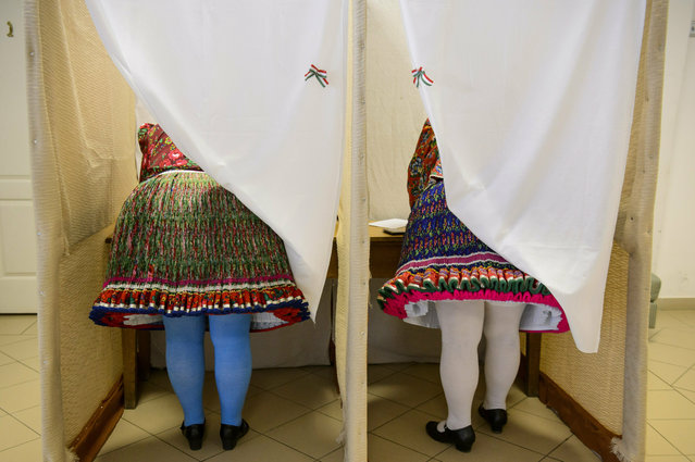 Women wearing folk costumes cast their vote during the European elections in a polling station in Bujak, Hungary, Sunday, May 26, 2019. The European Parliament election is held by member countries of the European Union (EU) from May 23 to 26, 2019. (Photo by Peter Komka/MTI via AP Photo)