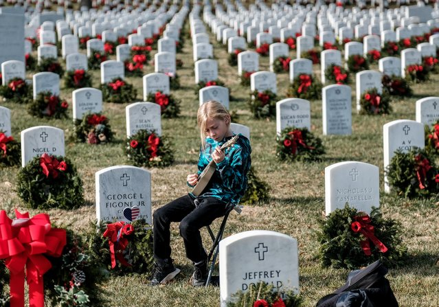 Armando Martin, 11 of California plays a guitar to honor GYSGT George Figone Jr. in Section 60 at Arlington National Cemetery in Arlington, Virginia, U.S. December 25, 2019. (Photo by Michael A. McCoy/Reuters)