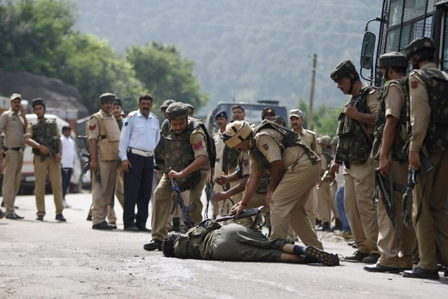Indian paramilitary soldiers check the body of a suspected rebel after a gunbattle on the Jammu- Srinagar highway at Narsoo Nallah, near Udhampur, India, Wednesday, August 5, 2015. Two paramilitary soldiers and one suspected rebel were killed in Indian-controlled Kashmir Wednesday after a convoy of paramilitary troops was ambushed in the troubled region, police said. (Photo by Channi Anand/AP Photo)