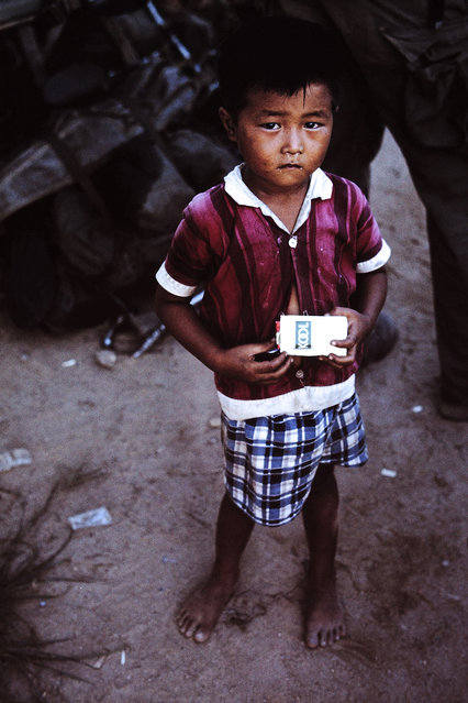"""A photograph by D. Thornton of a young Vietnamese boy holding a pack of """"Kool"""" cigarettes. (Photo by D. Thornton/The Vietnam Slide Project)"""