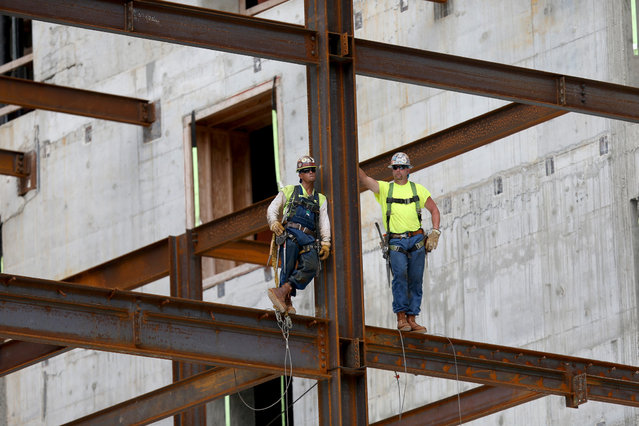 Construction workers build the $1.05 billion Brickell CityCentre condo/retail mix use complex in Miami, Florida, on Jule 7, 2014. Condo projects are booming in the South Florida area as foreign investors pour money into the new residences being built. (Photo by Joe Raedle/Getty Images)