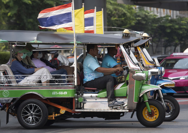 Tourists ride in tuk-tuks wearing face masks to protect from the poor air quality in Bangkok, Thailand, Monday, January 20, 2020. (Photo by Sakchai Lalit/AP Photo)