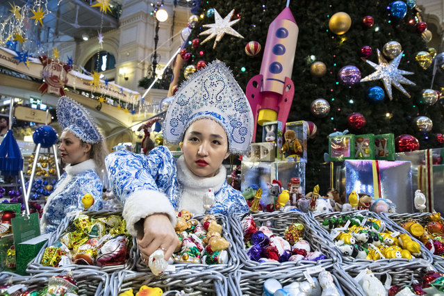 A seller dressed as Snegurochka (The Snow Maiden) shows Christmas toys at the Christmas decorations set in the Moscow GUM State Department store in Moscow, Russia in Moscow, Russia, Monday, December 16, 2019. (Photo by Pavel Golovkin/AP Photo)