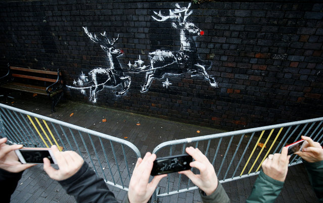 People gather round a new mural by the street artist Banksy in Birmingham, Britain, December 10, 2019. (Photo by Henry Nicholls/Reuters)