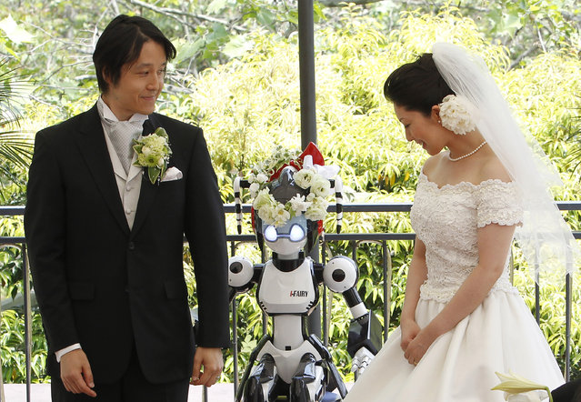 """A humanoid robot named """"I-Fairy"""" (C) acts as a witness at the wedding ceremony between Tomohiro Shibata (L) and Satoko Inoue in Tokyo May 16, 2010. The couple decided to use the robot, which conducted the ceremony with its audio functions, from Inoue's company to perform the witness' duties as they first met due to common work interest related to robots. (Photo by Yuriko Nakao/Reuters)"""