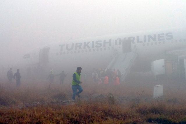 Passengers leave a Turkish Airlines plane which skidded off the runway on landing at Kathmandu airport in the Nepalese capital Kathmandu on March 4, 2015. Aviation officials said no one on board was injured, although one witness described how terrified passengers leapt from their seats as the cabin filled with smoke after the plane skidded to a halt. (Photo by Dikesh Malhotra/AFP Photo)