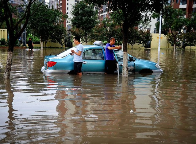A taxi driver and his passenger  get stuck in the floodwaters in Tianjin, China on July 26, 2012. (Photo by Associated Press)
